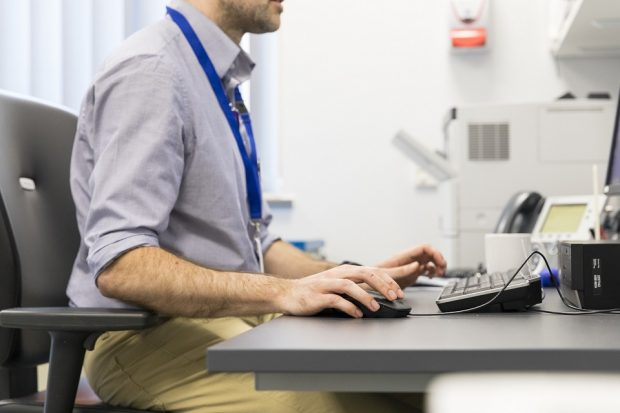 Close up of a male doctor working at a computer