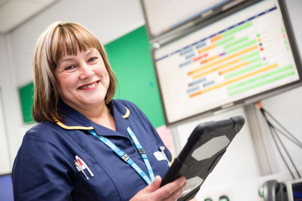 A theatre nurse using a tablet device
