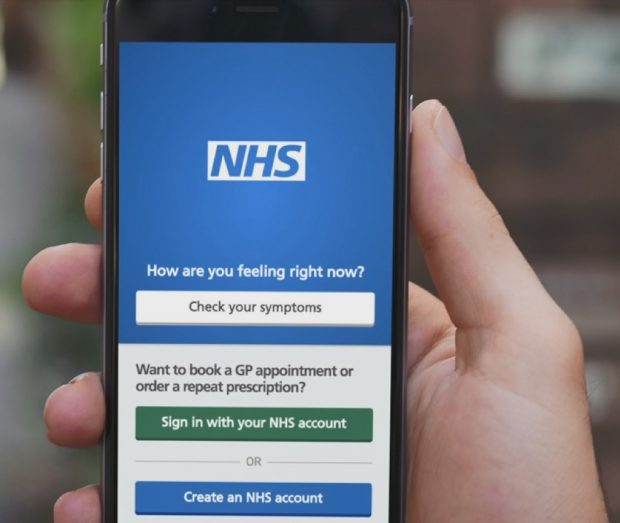 A hand holding a smart phone with the NHS app on the screen