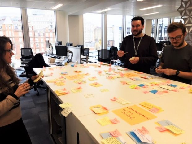3 people stood around a table with post it notes