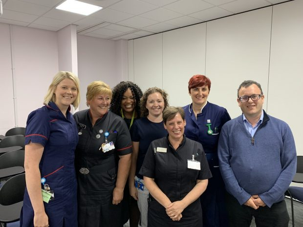 Six female NHS staff stand with Matthew Gould in a meeting room