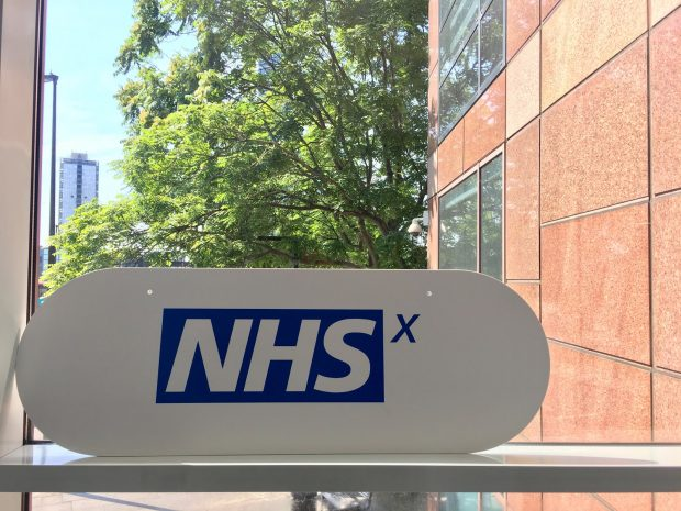 An NHSX sign on a window sill with a tree in the background